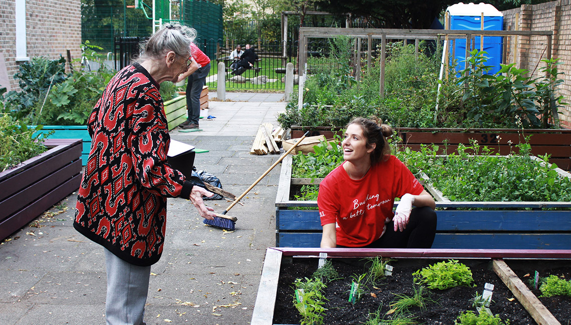 JLL volunteer chatting to resident in London community garden