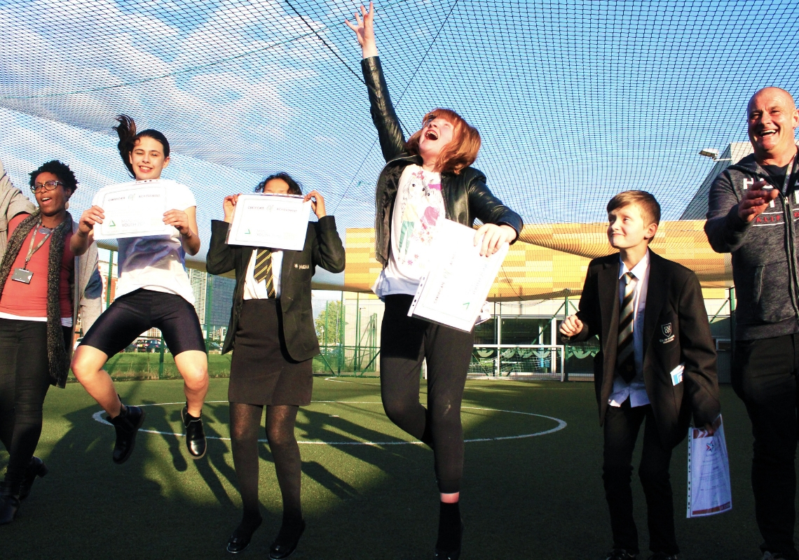 young people jumping for joy on a football pitch