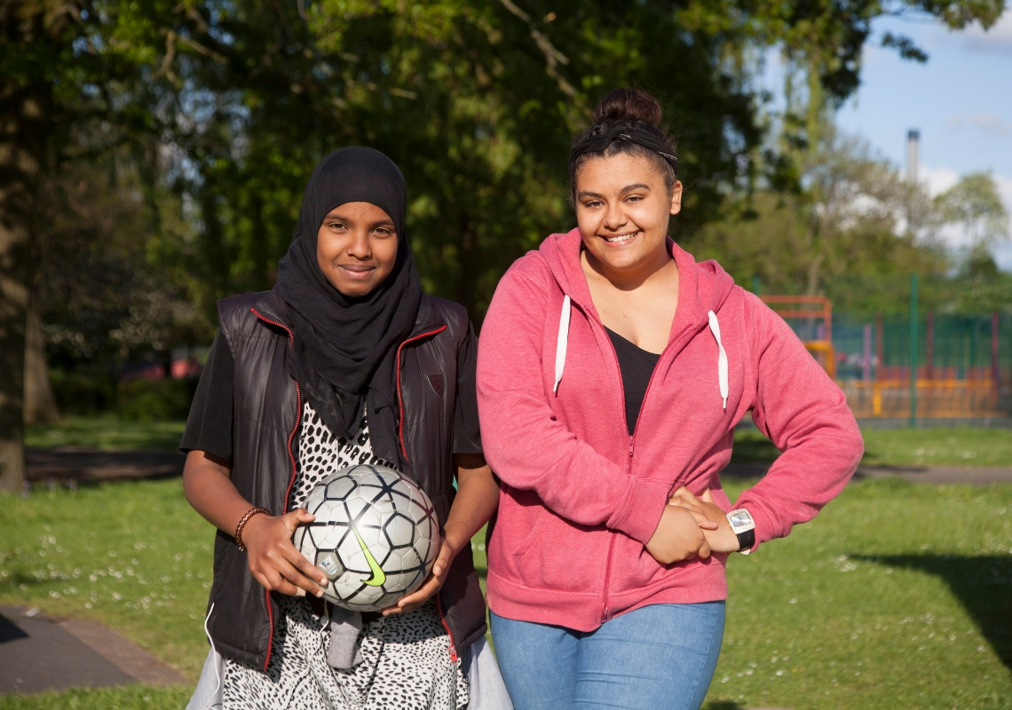 Two girls outside with a football