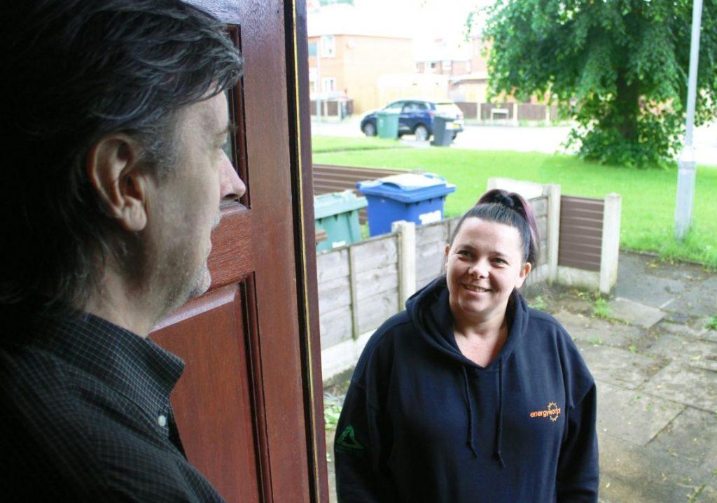 Energyworks employee talking to gentlemen on door step