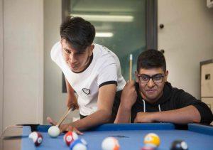 Two teenage boys playing pool