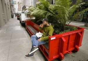 Man sitting on red box city parklet