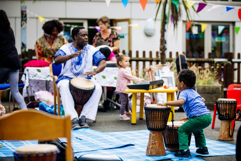 toddler playing drums at LEAP awardee's rhythm session