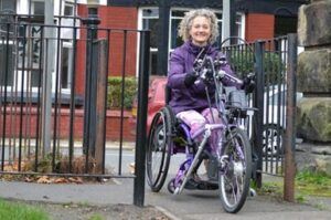 Woman using handcycle smiling as she goes through modified gate